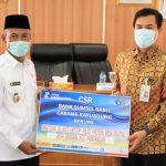 Kepala Bank Sumsel Babel Cabang Kayuagung, RM Rozali Anton saat menyerahkan 10 unit laptop sebagai dukungan program literasi digital di Ogan Komering Ilir, Kamis, (3/6)