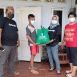 Relawan Slawi Gotong Royong menyerahkan bantuan paket sembako kepada salah seorang anggota keluarga dari yang sedang menjalani isolasi mandiri di Kabupaten Tegal, Kamis (22/7)