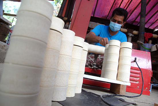 Perajin mengerjakan pembuatan tempat minum (tumbler) dari bahan bambu yang telah di ekspor ke negara Jerman di MQ Art Bamboo, Kelurahan Situgede, Kota Bogor, Jawa Barat, Senin (6/9/2021). Pemerintah akan memberikan stimulus dana untuk mendorong usaha mikro, kecil, dan menengah (UMKM) dalam mendukung Gerakan Nasional Bangga Buatan Indonesia (BBI) senilai Rp200 miliar yang diberikan kepada pelaku ekonomi kreatif subsektor fesyen, kuliner dan kriya. ANTARA FOTO/Arif Firmansyah/foc.
